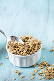 Almond Breakfast Cereal Granola In White Bowl With Spoon. Almond breakfast granola in white bowl on blue background with spoon royalty free stock photos