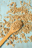 Almond Breakfast Cereal Granola On Wood Spoon And Spilled. Almond breakfast granola spilling around wooden spoon vertical royalty free stock image