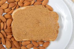 Almond butter on white bread on plate with almonds closeup Royalty Free Stock Image