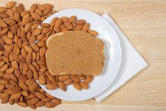 Almond butter on white bread on plate with almonds Royalty Free Stock Photography