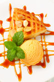 Almond cake with ice cream and caramel sauce Royalty Free Stock Images