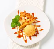 Almond cake with ice cream and caramel sauce Stock Images