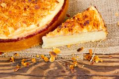 Almond cake. Photo of sliced almond cake on burlap and wooden board Stock Images