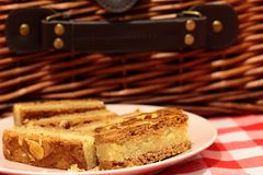 Almond cake slices on a plate with a picnic basket. On gingham fabric Stock Photography