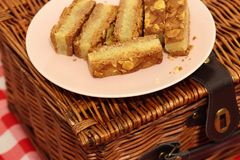 Almond cake slices on a plate with a picnic basket. On gingham fabric Stock Image