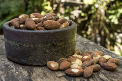 Almond and ceramic bowl. Almond in a ceramic bowl on a wooden table Royalty Free Stock Image