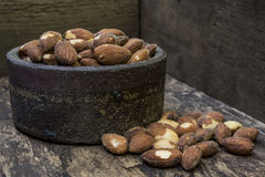Almond and ceramic bowl. Almond in a ceramic bowl on a wooden table Royalty Free Stock Photos