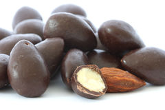 Almond in chocolate. Almonds covered in dark chocolate - one cut in half and one naked (without chocolate stock image