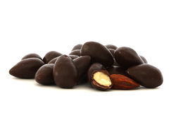 Almond in chocolate. Almonds covered in dark chocolate - one cut in half and one naked (without chocolate stock images
