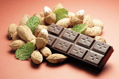Almond chocolate bar. Chocolate bar isolated on almond & mint leaf Royalty Free Stock Image