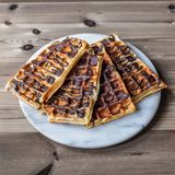 Almond chocolate waffles. Glazed with chocolate on a marble plate royalty free stock photography