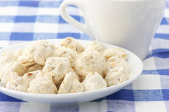 Almond cookies and cup. Almond cookies in white plate and white cup on checkered tablecloth Stock Photo