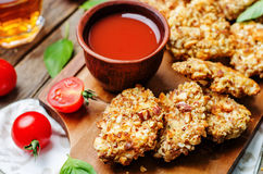 Almond crusted chicken tenders with tomato sauce. On dark wood background. toning. selective Focus Royalty Free Stock Image