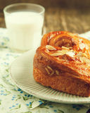 Almond Danish pastry on plate with glass of milk Royalty Free Stock Images