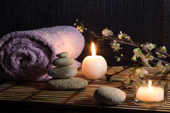 Almond flowers with candles, white stones on bamboo mat. For massage stock photo