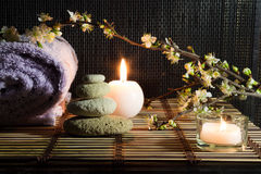 Almond flowers with towel, candles, white stones on bamboo mat. For massage stock image