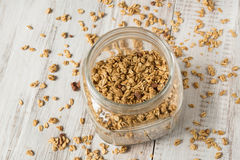 Almond Granola Breakfast Cereal In Glass Jar From Above. Almond breakfast granola in glass jar from above and spilled stock photo
