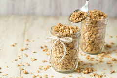 Almond Granola In Glass Jar With Spoon Scooping Stock Photo