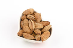 Almond in a heart shaped bowl on white bacaground Royalty Free Stock Photos