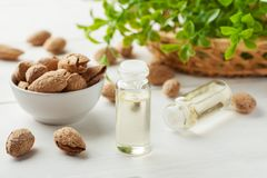 Free Almond In A White Bowl, Two Glass Bottles With Oil, Greenery In A Wicker Basket On A White Table Royalty Free Stock Images - 160649199