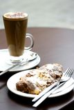Almond indulgence. A tall glass of cappucinno and an almond croissant on white plate Royalty Free Stock Photos
