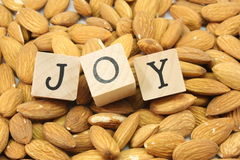 Almond Joy. A background of almonds with the word Joy in wood blocks Stock Photo