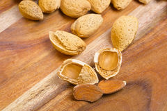 Almond kernel with shells on wooden background Stock Photography