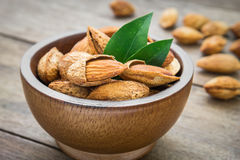 Almond with leaves in wooden bowl Royalty Free Stock Image