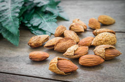 Almond with leaves on wooden table Stock Images