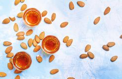 Almond liqueur with nuts on blue background, top view royalty free stock photo