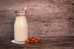 Almond milk. In a  bottle with strip straw and fresh almond on a wooden surface Royalty Free Stock Images