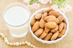 Almond milk in glass and almonds in white cup. Stock Images