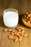Almond milk in glass with almonds in wooden bowl Royalty Free Stock Photo