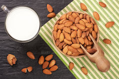 Almond milk in a glass and almonds in wooden bowl on black stone background. Top view.  Stock Photography
