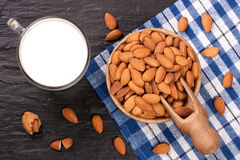 Almond milk in a glass and almonds in wooden bowl on black stone background. Top view.  Royalty Free Stock Images