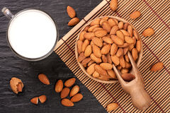 Almond milk in a glass and almonds in wooden bowl on black stone background. Top view.  Royalty Free Stock Image
