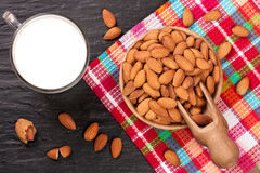 Almond milk in a glass and almonds in wooden bowl on black stone background. Top view.  Stock Images