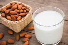 Almond milk in glass with almonds on wooden table Stock Images