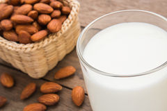 Almond milk in glass with almonds on wooden table Stock Image
