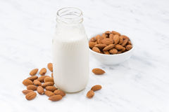 Almond milk in a glass bottle on white table Royalty Free Stock Image