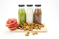 Almond milk in glass bottles. With almonds and apple Royalty Free Stock Photos