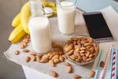 Almond milk in a glass Cup and fruit with scattered almonds on the kitchen table. Diet healthy vegetarian product stock photography