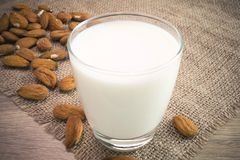 Almond milk. A glass of almond milk with seeds on wooden table Stock Photography