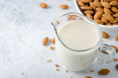 Almond milk in a milk pitcher. With almond nuts on a light stone background. High angle view, horizontal image, copy space Royalty Free Stock Photo