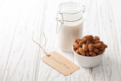 Almond milk organic healthy nut vegan vegetarian drink. White background wood teak rustic still life label Royalty Free Stock Image