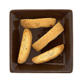 Almond nut biscotti on a brown plate top view. Top view of four almond nut biscotti on a square brown plate isolated on a white background Royalty Free Stock Photo