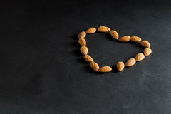 Almond nuts forming a heart-shape on black background Stock Photos