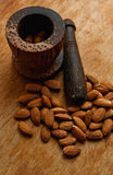 Almond nuts and a ponder on a wooden desk Royalty Free Stock Photos