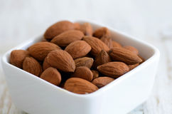 Almond nuts. Raw peeled almond nuts in a ceramic bowl Stock Photos