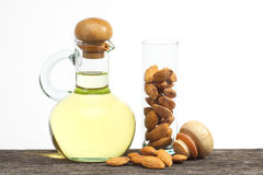 Almond oil. In bottle glass with seed on the old plank wood Royalty Free Stock Images